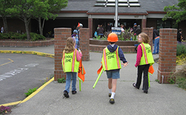Children walking in a school zone wearing reflective vests