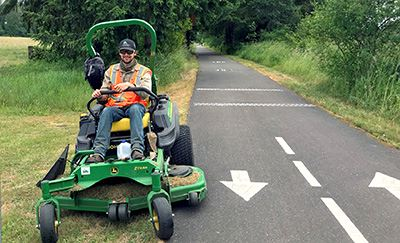 Photo of public works employee mowing vegetation along paved Yelm-Tenino Trail.