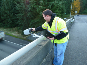 A city worker monitoring traffic flow from an overpass