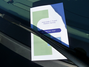 A flyer is placed under the windshield wiper of a car